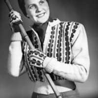 Mode från Nordiska Kompaniet. Modell i stickad kofta (så kallad Bohusstickning), kjol, halsduk, jersey-turban och vantar håller i en käpp.