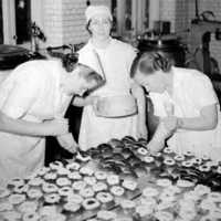 Äldre bild på kökspersonal i färd med bak av semlor